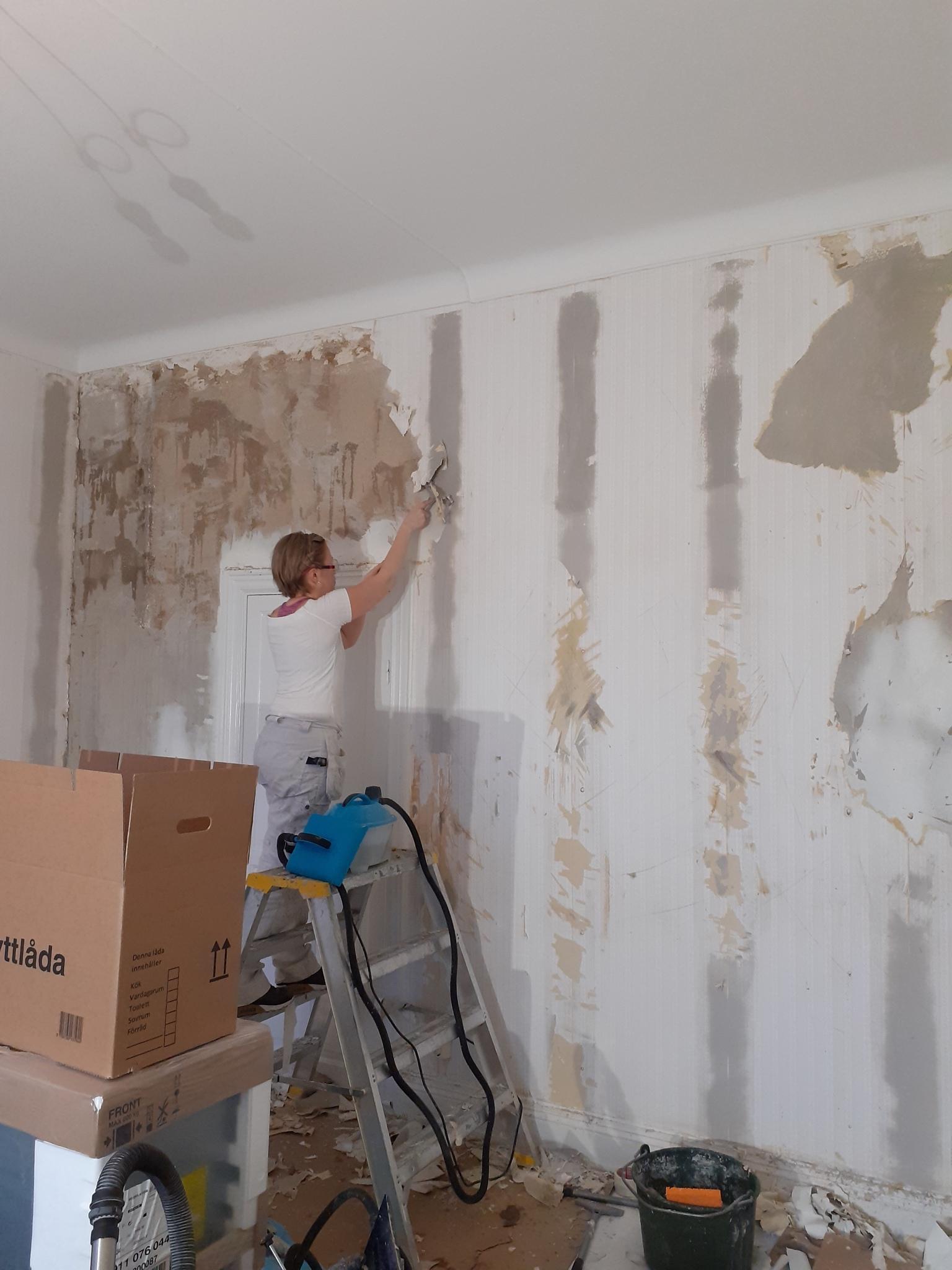 Vardagsrum i sekelskifte på Kungsholmen med nedtagning av alla lager tapet innan målning