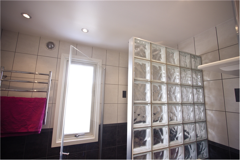 Klassiskt badrum med dekårplattor, tvättmaskin och glasbetong vägg